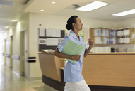 Nurse rushing in hospital hallway - CAIF03441