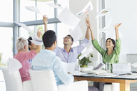 Business people tossing papers in air in meeting - CAIF03462