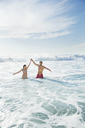 Couple standing in ocean with arms raised - CAIF03522
