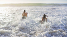 Couple surfing in ocean - CAIF03528