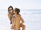 Happy couple hugging on beach - CAIF03537