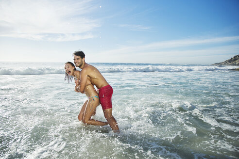 Enthusiastic couple hugging and splashing in ocean - CAIF03555