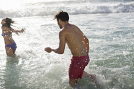 Couple splashing in ocean - CAIF03558