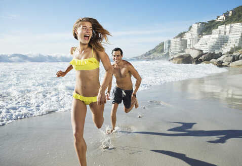 Man chasing happy woman on beach - CAIF03564