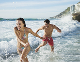 Playful couple splashing in ocean surf - CAIF03567