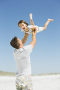 Father lifting daughter overhead on beach - CAIF03576