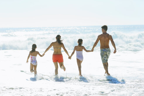 Family running into surf at beach - CAIF03582