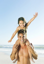 Father carrying daughter on shoulders at beach - CAIF03588