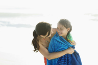 Mother wrapping daughter in towel on beach - CAIF03594