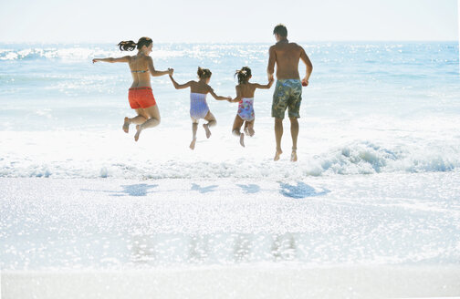 Family jumping in surf at beach - CAIF03609