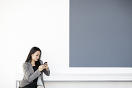 Businesswoman using cell phone in office - CAIF03624