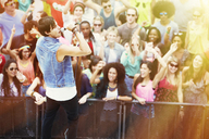 Fans cheering for singer performing on stage at music festival - CAIF03627