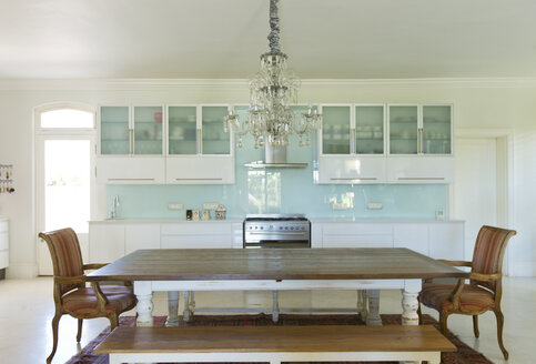 Chandelier over wooden table in kitchen - CAIF03678