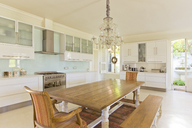 Chandelier over wooden table in kitchen - CAIF03696