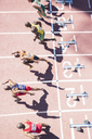 Sprinters taking off from starting blocks on track - CAIF03717