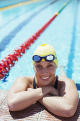 Portrait of smiling swimmer leaning at edge of pool - CAIF03777