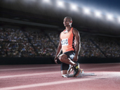 Runner with feet in starting block on track - CAIF03792