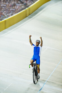 Track cyclist celebrating in velodrome - CAIF03804