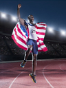 Runner holding American flag and celebrating on track - CAIF03810
