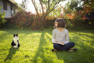 Smiling girl sitting on meadow with a book next to cat - LVF06751