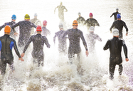 Triathletes in wetsuits running into ocean - CAIF03814