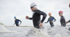 Triathletes in wetsuits running in waves - CAIF03835