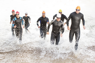 Triathletes in wetsuits running in waves - CAIF03841
