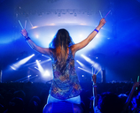 Cheering woman with glow sticks on manÍs shoulders at music festival - CAIF03880