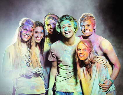 Portrait of friends covered in chalk dye at music festival - CAIF03883