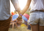 Couple holding hands near tents at music festival - CAIF03886