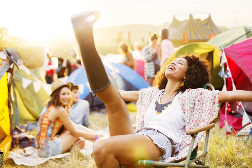 Carefree woman outside tents at music festival - CAIF03889