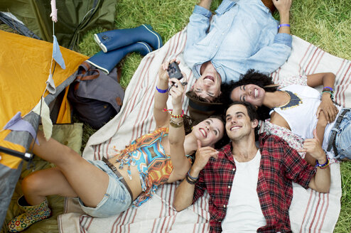Friends taking self-portrait on blanket outside tent at music festival - CAIF03895