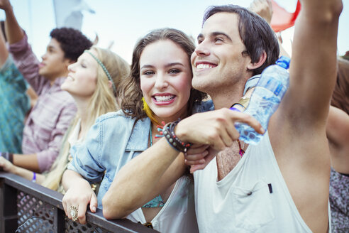 Couple cheering at music festival - CAIF03913