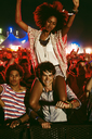 Cheering woman on manÍs shoulders at music festival - CAIF03916