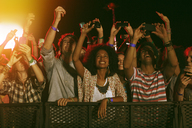 Fans with camera phones cheering at music festival - CAIF03925