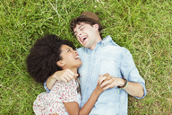 Laughing couple laying in grass - CAIF03928