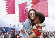 Enthusiastic couple hugging at music festival - CAIF03934