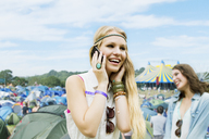 Woman talking on cell phone outside tents at music festival - CAIF03940