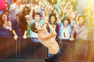 Fans cheering for performer singing on stage - CAIF03970