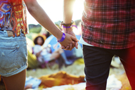 Close up of couple holding hands outside tents at music festival - CAIF03976
