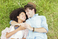 Happy couple holding hands and laying in grass - CAIF03988