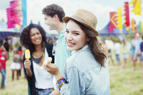 Portrait of woman eating flavored ice with friends at music festival - CAIF03994
