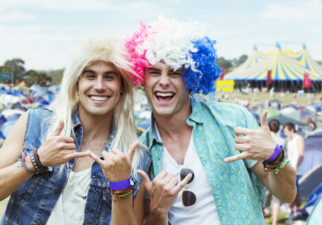 Portrait of men in wigs gesturing at music festival - CAIF04000