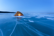 Russia, Amur Oblast, illuminated tent on frozen Zeya River at blue hour - VPIF00375