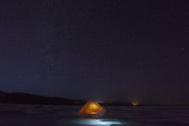 Russia, Amur Oblast, illuminated tent on frozen Zeya River at night under starry sky - VPIF00378