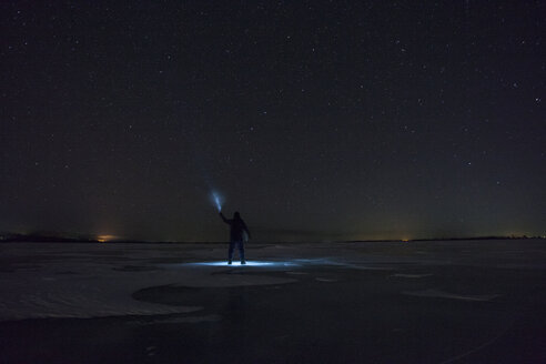 Russia, Amur Oblast, silhouette of man with blue ray standing on frozen Zeya River at night under starry sky - VPIF00381