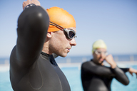 Triathlete tying on goggles outdoors - CAIF04055
