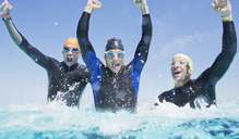 Triathletes in wetsuits splashing in waves - CAIF04061