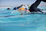 Triathletes in wetsuit splashing in pool - CAIF04079