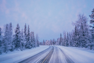 Remote winter road through snow covered forest trees against blue sky, Lapland, Finland - CAIF04151